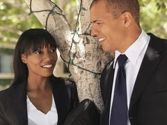 A businesswoman and businessman leaning against a tree and talking - stock photo