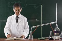 A chemistry teacher conducting an experiment in a classroom - stock photo