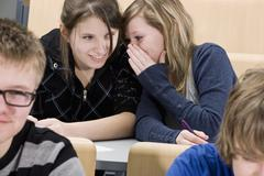 Two female high school students whispering in class - stock photo