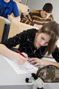 A female high school student doing school work in a classroom Stock Photos