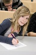Portrait of a teenager doing a worksheet in class, smiling at camera Stock Photos