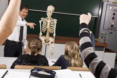 A teacher points while his students raise their hands in a biology class - stock photo