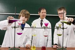 A teacher supervising two students conducting a chemistry experiment - stock photo
