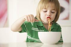 Stock Photo of A boy eating spaghetti