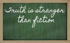 expression -  truth is stranger than fiction - written on a school blackboard - stock photo