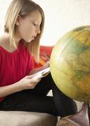 A girl writing in a notepad while sitting next to a world globe Stock Photos