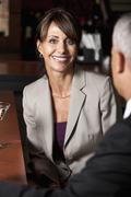 A businesswoman sitting opposite a colleague at a bar Stock Photos
