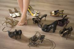 A woman standing in the middle of several pairs of shoes, low section Stock Photos