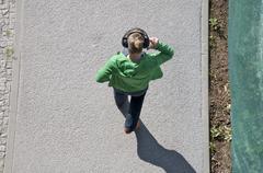 A woman wearing headphones walking on a sidewalk Stock Photos
