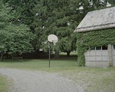 A basketball hoop next to a garage Stock Photos