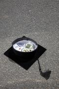 Mortarboard with money in it on asphalt Stock Photos