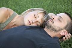 Man and woman sleeping on grass Stock Photos