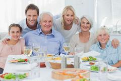 Stock Photo of Extended family smiling at dinner family
