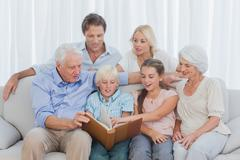 Stock Photo of Extended family looking at a photo album