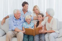 Stock Photo of Extended cheerful family looking at a photo album