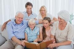 Stock Photo of Extended family looking at an album photo