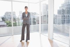 Businesswoman standing in bright office - stock photo