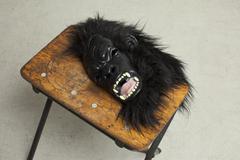 A fancy dress mask lying on a stool Stock Photos