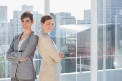 Stock Photo of Businesswomen standing back to back