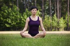 A woman sitting cross-legged on grass, eyes closed Stock Photos