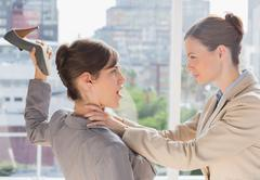 Businesswoman defending herself from her co worker strangling her Stock Photos