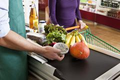 A cashier and customer at the checkout line of a supermarket, midsection Stock Photos