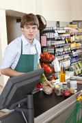 A cashier working in a supermarket - stock photo