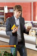 A man contemplation two products in a supermarket - stock photo