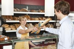 A sales clerk helping a customer at a bakery - stock photo