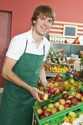 A grocery stocker stocking apples - stock photo
