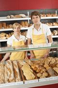Two sales clerks behind the counter at a bakery Stock Photos