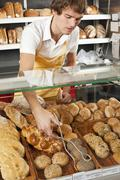 A sales clerk picking up a roll with tongs in a bakery Stock Photos