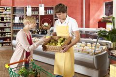A customer and grocer in a supermarket Stock Photos