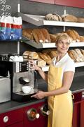 A sales clerk using an espresso maker in a bakery cafe - stock photo