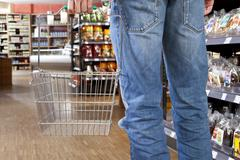 A man in a supermarket with an empty shopping basket, low section - stock photo
