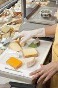 A sales clerk preparing wedges of cheese - stock photo