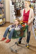 A mother and daughter shopping at the supermarket Stock Photos
