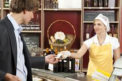 A sales clerk handing a customer a wedge of cheese - stock photo