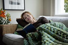 A woman reading a book while reclining on a sofa Stock Photos