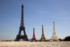 Three Eiffel Tower replica souvenirs next to the real Eiffel Tower, focus on Stock Photos