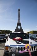 A car decorated with flowers and ribbons in front of the Eiffel Tower Stock Photos