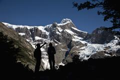 Two people in silhouette standing below snowy mountains, Torres del Paine - stock photo