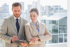 Smiling business partners going over document on clipboard - stock photo