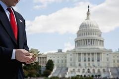 Stock Photo of A politician counting money in front of the US Capitol Building