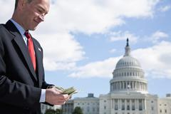 A politician counting money in front of the US Capitol Building - stock photo
