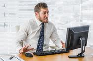 Stock Photo of Frustrated businessman looking at his computer