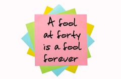 "Stock Photo of proverb ""a fool at forty is a fool forever"" written on bunch of sticky notes"