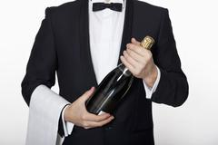 A sommelier holding a bottle of champagne Stock Photos