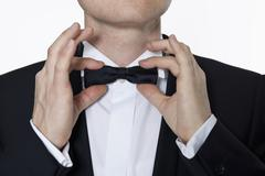 A man wearing a tuxedo adjusting his bow tie, focus on hands Stock Photos