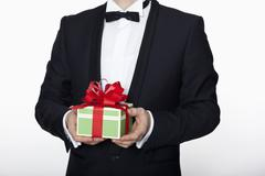 A man in a tuxedo holding a birthday gift, midsection - stock photo
